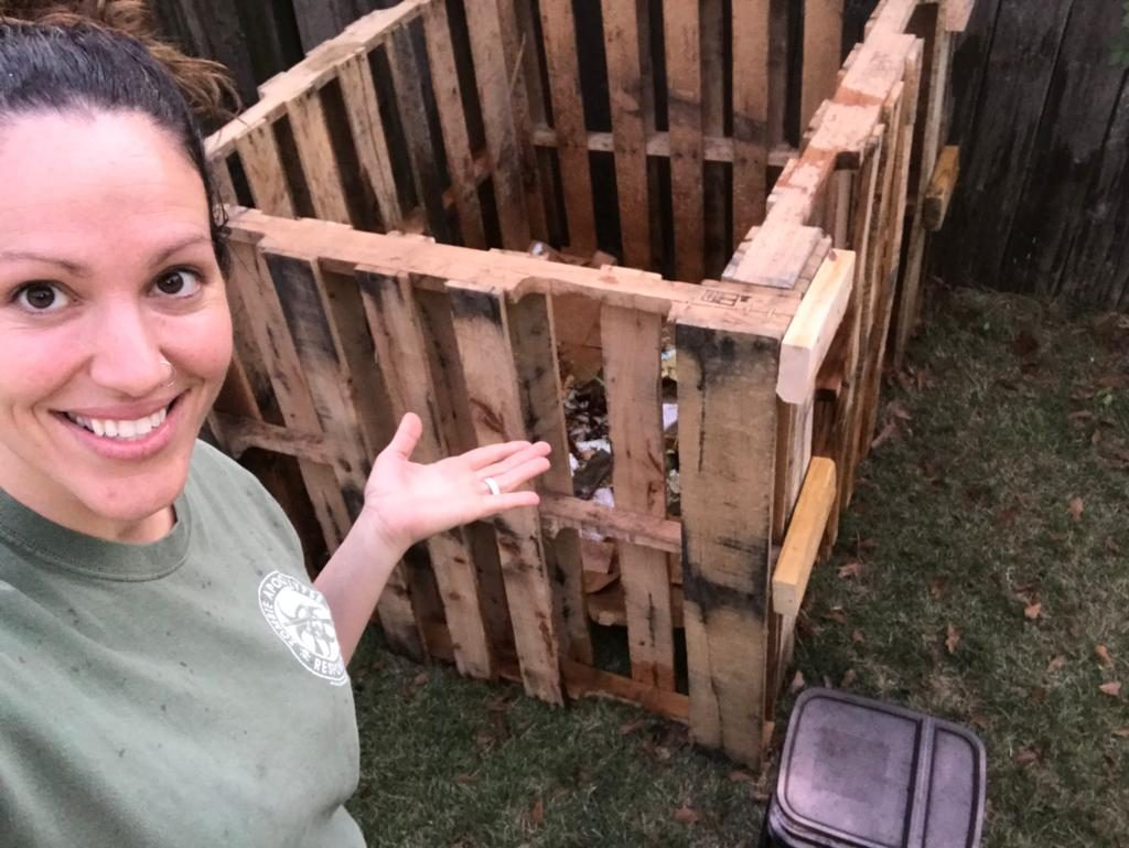 simple compost bin from pallets, pretty woman in foreground